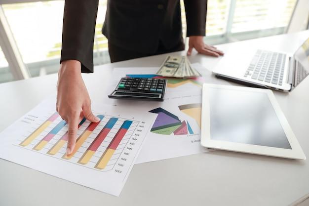 Bizneswoman używa pastylkę i komputer podczas gdy pracujący na firmy zbiorczym raporcie z wykresem Premium Zdjęcia