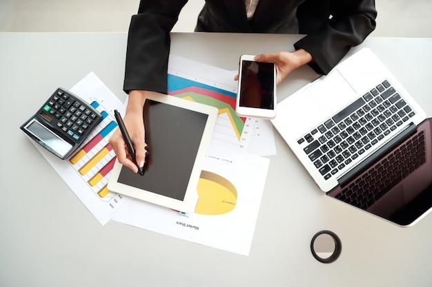 Bizneswoman używa telefon komórkowego i komputer podczas gdy pracujący na firmy zbiorczym raporcie z wykresem Premium Zdjęcia
