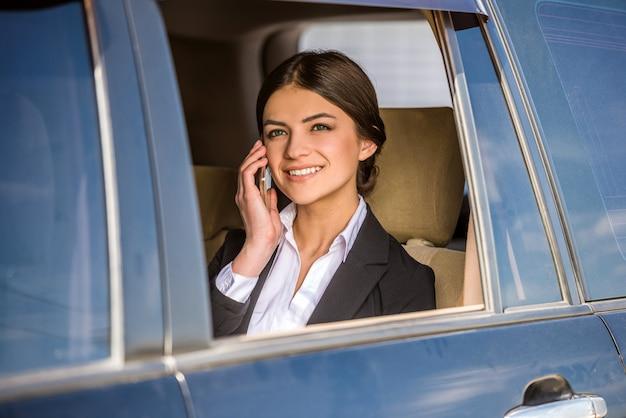 Bizneswoman w kostiumu obsiadaniu w jej luksusowym. Premium Zdjęcia