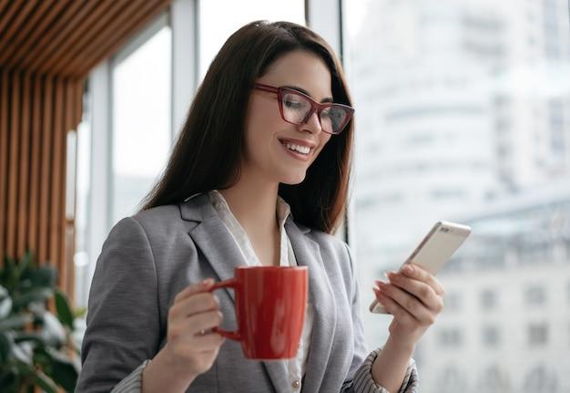 Bizneswomanu Mienia Telefon Komórkowy, Filiżanka Kawy, Komunikacja, Robi Zakupy Online Premium Zdjęcia