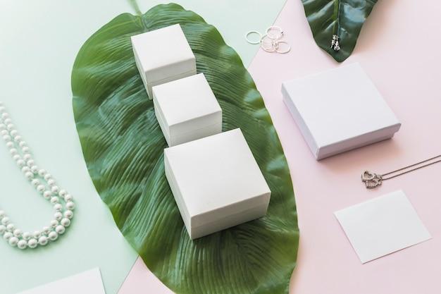 Biżuteria Z Białymi Pudełkami Na Zielonym Liściu Nad Papierowym Tłem Darmowe Zdjęcia
