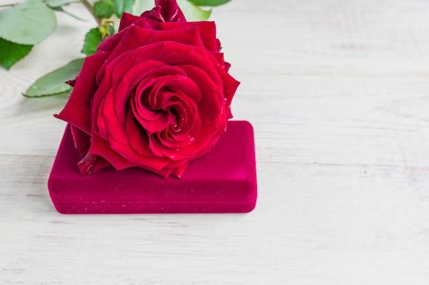Biżuterii prezenta pudełko i bautiful czerwieni róża na drewnianym tle. Premium Zdjęcia