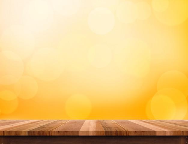 Blat z drewna deski na pomarańczowym tle światła bokeh Premium Zdjęcia