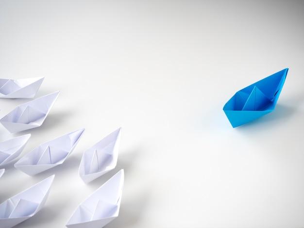 Błękitna papierowa łódź prowadzi wśród białych statków Premium Zdjęcia