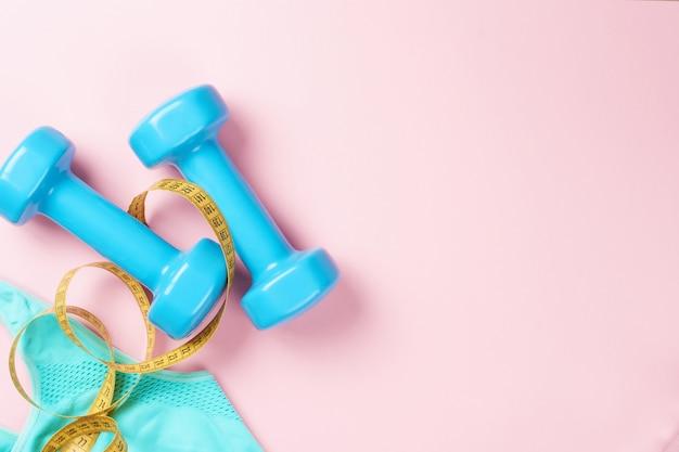 Błękitni dumbbells i sporta stanik na różowym tle, odgórny widok z kopii przestrzenią Premium Zdjęcia