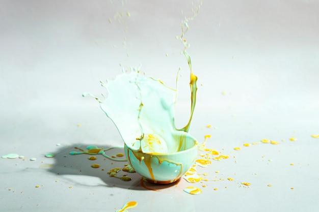 Błękitny i żółty farby pluśnięcie i filiżanka abstrakta tło Darmowe Zdjęcia