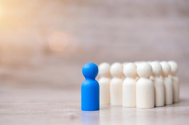 Błękitny lidera biznesmen z tłumem drewniani mężczyzna. przywództwo, biznes, zespół, praca zespołowa i zarządzanie zasobami ludzkimi Premium Zdjęcia