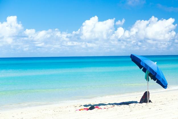 Błękitny Parasol Z Torbą I Ręcznikiem Na Ocean Plaży Z Pięknym Niebieskim Niebem I Chmurami Premium Zdjęcia