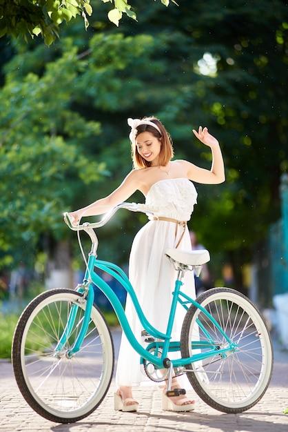 Błękitny Retro Rowerowy Pobliski Piękna Dziewczyna W Lata świetle Słonecznym Premium Zdjęcia