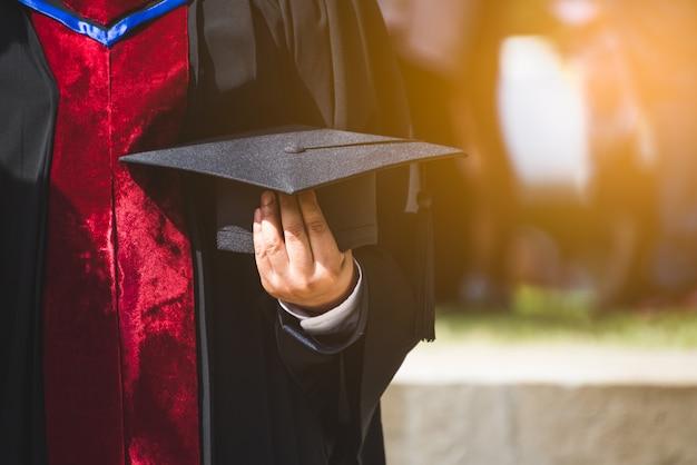 Bliska Absolwent Trzyma Kapelusz. Kształcenie W Zakresie Sukcesów Na Uniwersytecie Premium Zdjęcia