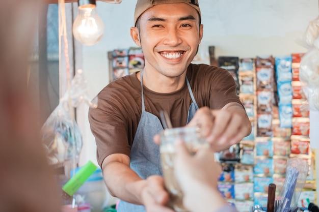 Bliska Asian Człowiek Sprzedawca Stoisko Z Wózkiem W Fartuchu Daje Napoje Klientom Na Straganie Z Wózkiem Premium Zdjęcia