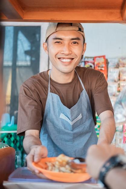 Bliska Azjatycki Sprzedawca Młody Mężczyzna, Sklep Z Wózkiem Uśmiecha Się, Obsługując Klientów Przy Stoisku Z Wózkami Premium Zdjęcia