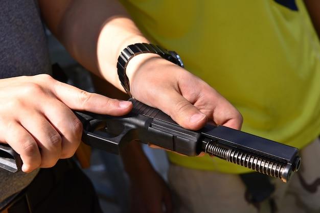 Bliska Człowieka Montaż Demontażu Części Pistoletu Konserwacyjnego W Strefie Bezpieczeństwa Na Strzelnicy Premium Zdjęcia