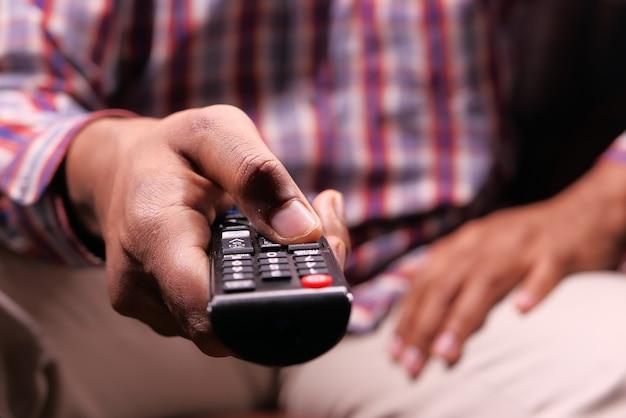 Bliska Człowieka Ręki Trzymającej Pilota Do Telewizora. Premium Zdjęcia