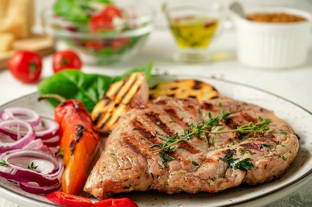 Bliska Grillowany Stek Z Ziołami, Przyprawami I Warzywami Na Talerzu Premium Zdjęcia