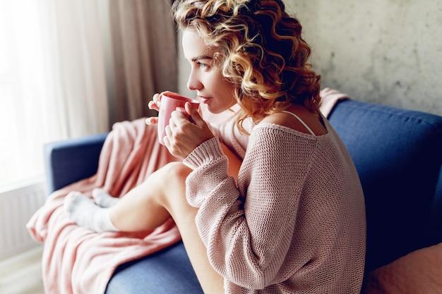 Bliska Kryty Portret Wdzięcznej Blondynki Kobiety Cieszącej Się Zapachem Cappuccino, Marzy I Patrząc W Okno. Ubrana W Różowy Sweter Z Dzianiny. Darmowe Zdjęcia