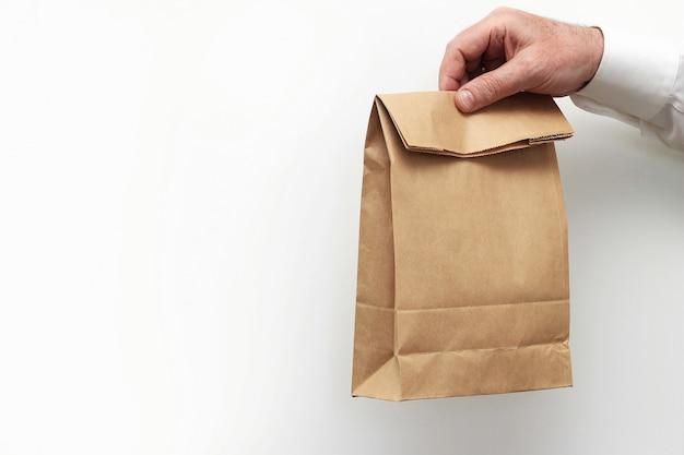 Bliska Mężczyzna Trzyma W Ręku Jasne Puste Puste Rzemiosło Papierową Torbę Na Wynos Premium Zdjęcia