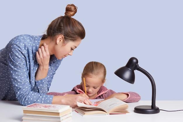 Bliska Młoda Mama Pomaga Napisać Córkę, Aby Napisać Skład, Użyć Lampki Do Czytania, Dziewczyny Wyglądają Na Skoncentrowane, Odizolowane Na Białym. Koncepcja Dzieci I Uczenia Się. Darmowe Zdjęcia