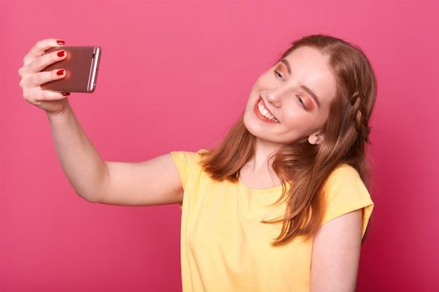 Bliska Młode Stylowe Kobiety Robiące Selfie, Używając Własnego Smartfona, Ubrana Na Co Dzień żółta Koszulka, Ma Proste Włosy, Chce Nowego Zdjęcia Do Sieci Społecznościowych. Darmowe Zdjęcia