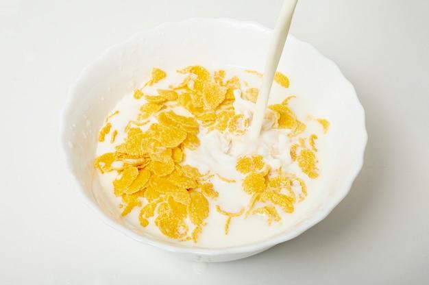 Bliska Nalewania Mleka W Misce Z Płatkami Kukurydzianymi Darmowe Zdjęcia