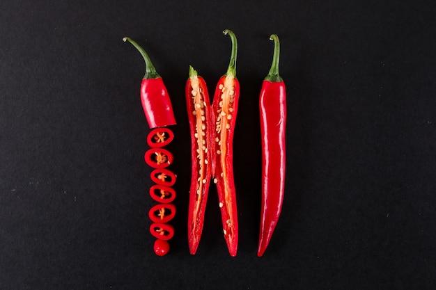 Bliska Plasterki Czerwonej Papryki Chili Odizolowane Na Czarnej Powierzchni Darmowe Zdjęcia