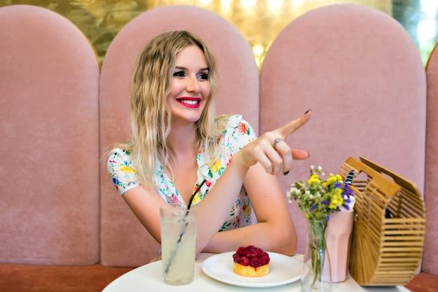 Bliska Portret Kryty ładny Blond Kobieta Pozuje W Restauracji, Je Smaczne Ciasto I Pokazuje Coś Palcem, Słodkie Dziewczęce Wnętrze, Wesołe Emocje. Darmowe Zdjęcia