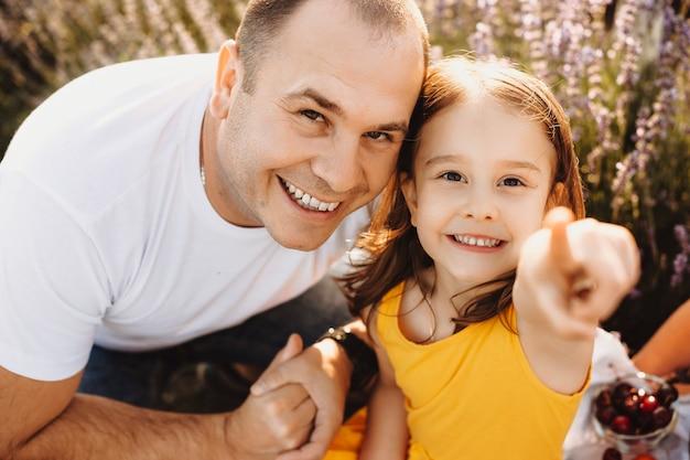Bliska Portret Pięknej Małej Dziewczynki Ubranej W żółtą Sukienkę, Patrząc Na Kamery, Obejmując Z Ojcem I Wskaż Aparat W Polu Z Kwiatami. Premium Zdjęcia