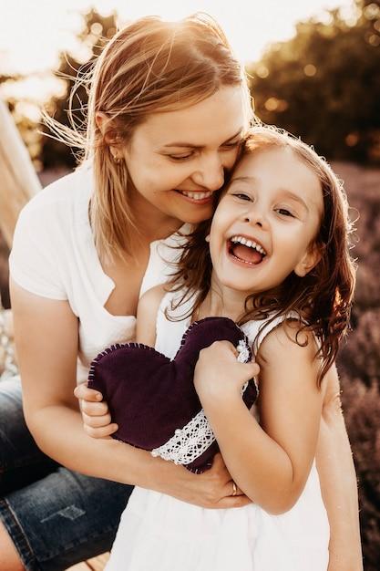 Bliska Portret Pięknej Matki I Córki Obejmując I śmiejąc Się, Patrząc Na Kamery Przed Zachodem Słońca W Polu Z Kwiatami. Premium Zdjęcia