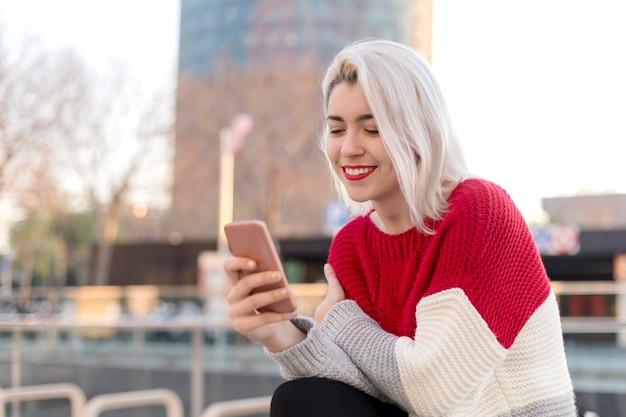 Bliska Portret Pięknej Młodej Kobiety Za Pomocą Telefonu Komórkowego Na Zewnątrz W Mieście Premium Zdjęcia