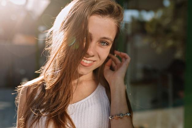 Bliska Portret Szczęśliwa Uśmiechnięta Dziewczyna Z Długimi Włosami I Niebieskimi Oczami Pozuje Do Kamery W Słońcu Darmowe Zdjęcia
