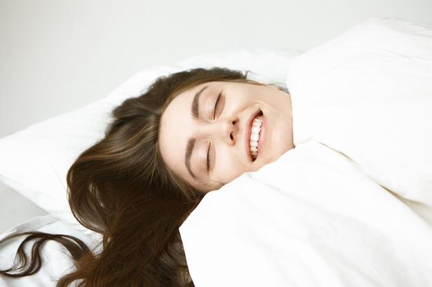 Bliska Portret Szczęśliwej Beztroskiej Młodej Kobiety Rasy Kaukaskiej Z Lśniącymi Włosami Brunetki Zamykającymi Oczy Z Przyjemnością, Relaksując Się W łóżku Owiniętym Białym Kocem, Czując Się Ciepło I Wygodnie W Mroźny Zimowy Dzień Darmowe Zdjęcia