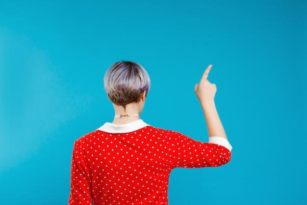 Bliska Portret Z Tyłu Piękna Lalka Dziewczyna Z Krótkimi Jasnofioletowymi Włosami Na Sobie Czerwoną Sukienkę, Wskazując Palcem Na Niebieską ścianą Darmowe Zdjęcia