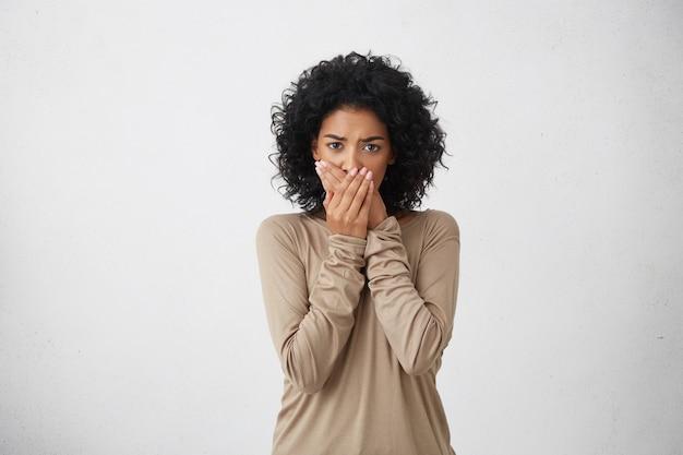 Bliska Portret Zdenerwowanej, Przestraszonej Czarnej Kobiety, Zakrywającej Usta Dłońmi, Aby Zapobiec Krzyczeniu Po Zobaczeniu Lub Usłyszeniu Czegoś Złego. Negatywne Emocje, Mimika I Uczucia Darmowe Zdjęcia