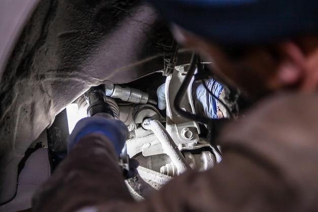 Bliska Profesjonalny Mechanik Samochodowy Naprawia Podwozie Obsługiwanego Samochodu W Serwisie Samochodowym. Autoworker Zmienia Rękawy W Garażu Stacji Naprawczej Premium Zdjęcia