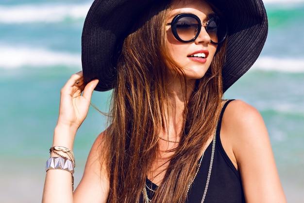 Bliska Słoneczny Letni Portret Pięknej Kobiety Z Puszystymi Brunetkami Długimi Włosami, Uśmiechnięta, Bawiąca Się W Pobliżu Błękitnego Oceanu, Nosząca Okulary Przeciwsłoneczne, Strój I Kapelusz, Styl Wakacyjny, Jasne Kolory Darmowe Zdjęcia
