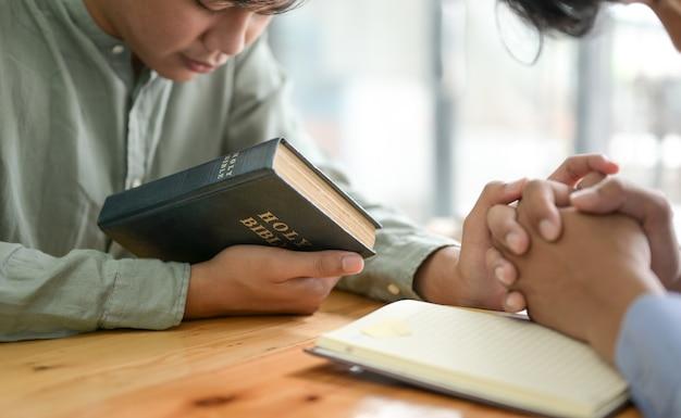 Bliska Strzał Biblii I Modlących Się Ludzi Premium Zdjęcia