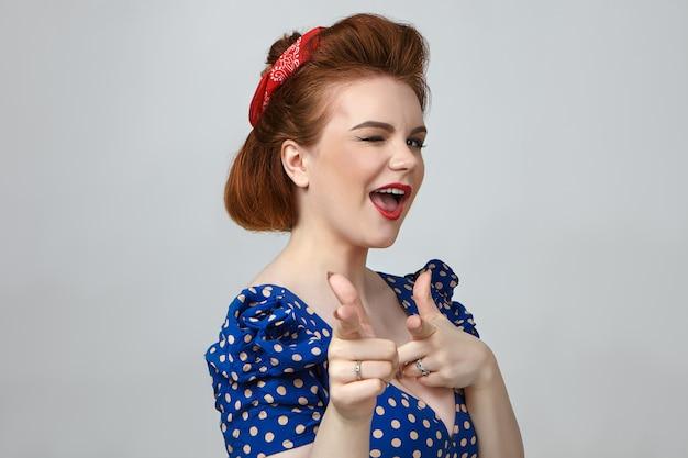 Bliska Strzał Glamour Atrakcyjna Młoda Brunetka Kobieta W Sukienka Vintage Kropkowane Mruganie I Wskazujące Palce Wskazujące Darmowe Zdjęcia