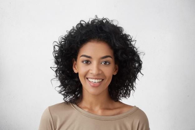 Bliska Strzał ładna Kobieta Z Doskonałymi Zębami I Ciemną, Czystą Skórą Odpoczywającą W Pomieszczeniu, Uśmiechnięta Radośnie Po Otrzymaniu Dobrych, Pozytywnych Wiadomości. Darmowe Zdjęcia