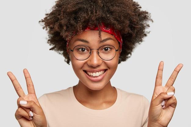 Bliska Strzał Piękna Wesoła Ciemnoskóra Młoda Kobieta Z Kręconymi Włosami Sprawia, że Znak Pokoju Obiema Rękami Darmowe Zdjęcia