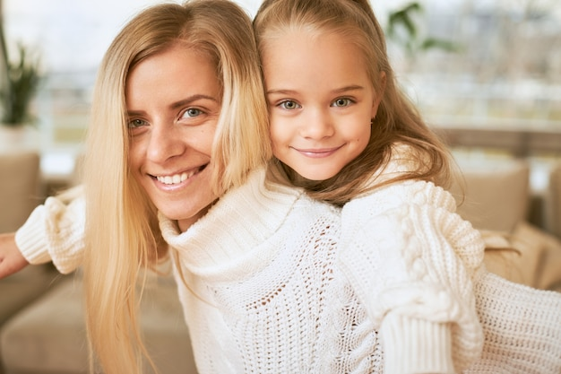 Bliska Strzał Radosnej Młodej Blondynki W Białym Swetrze, Oddając Przejażdżkę Swojej Uroczej Córeczce Spędzającej Zimowy Grudniowy Dzień W Domu, śmiejąc Się, Wiążąc I Zabawiając Się Darmowe Zdjęcia