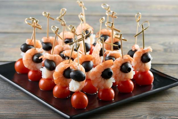 Bliska Strzał świeże Krewetki Podawane Z Pomidorkami Cherry I Czarnymi Oliwkami Na Drewnianym Stole W Luksusowej Restauracji Cafe Przystawka Owoce Morza Warzywa Zdrowe Odżywianie Jedzenie. Darmowe Zdjęcia