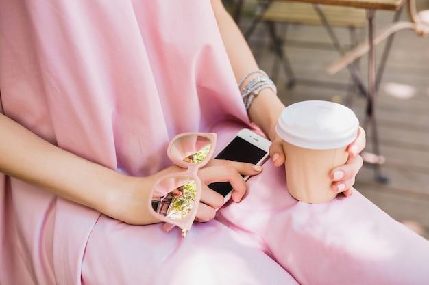 Bliska Szczegóły Rąk Kobiety Siedzącej W Kawiarni W Letnim Stroju Modowym, Stylu Hipster, Różowej Bawełnianej Sukience, Okularach Przeciwsłonecznych, Piciu Kawy, Stylowych Akcesoriach, Relaksującej, Modnej Odzieży Darmowe Zdjęcia