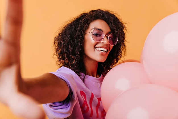 Blithesome Girl Z Falującymi Włosami Pozuje Z Podekscytowaniem Na Pomarańczowo. Jocund Afrykańska Kobieta Robi Selfie Z Balonów Helem. Darmowe Zdjęcia