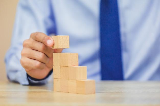 Bliżej ręce biznesmenów, układając drewniane klocki w kroki. Premium Zdjęcia