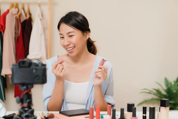 Bloger Piękności Prezentuje Kosmetyki Kosmetyczne Siedząc W Przedniej Kamerze Do Nagrywania Wideo. Darmowe Zdjęcia