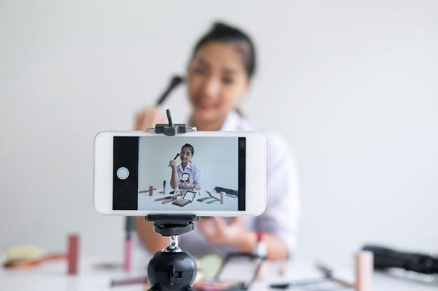 Blogerka Beautiful Asian Kobieta, Prowadząca Działalność Online W Mediach Społecznościowych, Pokazuje Obecny Produkt Kosmetyczny Z Samouczkiem I Transmituje Na żywo Wideo Do Sieci Społecznościowej Podczas Nagrywania Nauczania Online Premium Zdjęcia
