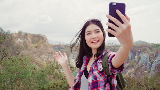 Blogger asian backpacker kobieta nagrywa wideo vlog na szczycie góry, młoda kobieta szczęśliwa przy użyciu telefonu komórkowego sprawia, że vlog video cieszy się wakacjami na wędrówce. Darmowe Zdjęcia