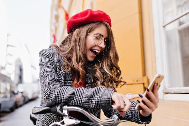 Błogi Biała Kobieta Z Brunetką Patrząc Na Ekran Telefonu Z Uśmiechem Na Tle Ulicy Darmowe Zdjęcia