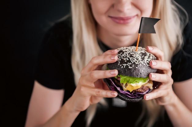 Blond Dziewczyna W Czarnej Koszulce Z Wielkim Czarnym Burgerem W Dłoniach Premium Zdjęcia