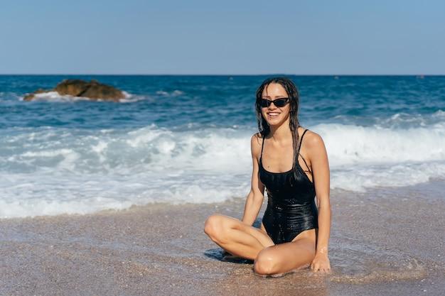Blond dziewczyna w swimsuit obsiadaniu przy morze plaży opalaniem Darmowe Zdjęcia